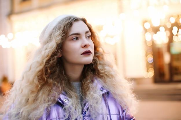 Portret van jonge mooie vrouw met krullend blondie haar buitenshuis. schoonheid, mode-concept. street style. bokeh achtergrond