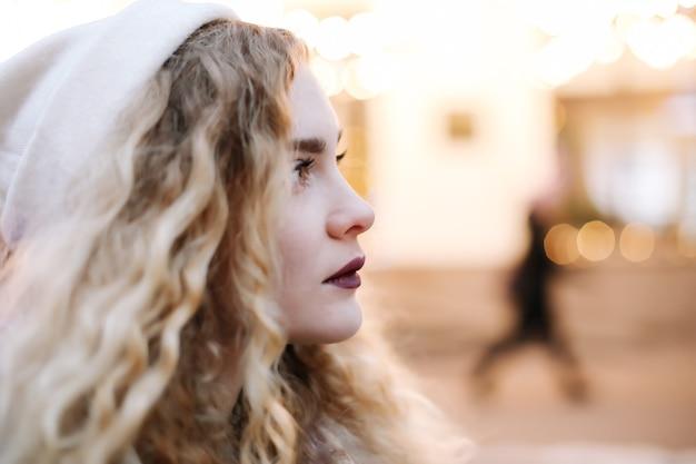 Portret van jonge mooie vrouw met krullend blondie haar buitenshuis. schoonheid, mode-concept. street style