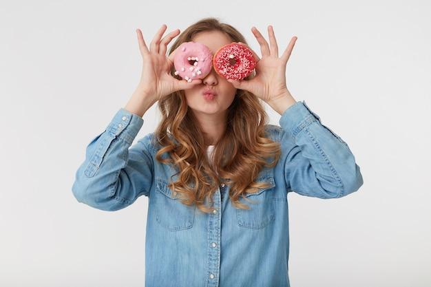 Portret van jonge mooie vrouw met lang blond golvend haar, die een denimoverhemd draagt, door donuts kijkt en een kus verzendt, die over witte achtergrond wordt geïsoleerd.