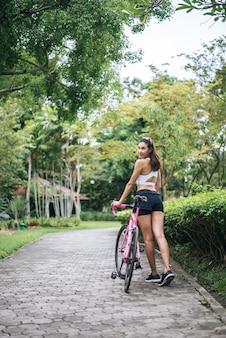 Portret van jonge mooie vrouw met roze fiets in het park. actractive gezonde vrouw.