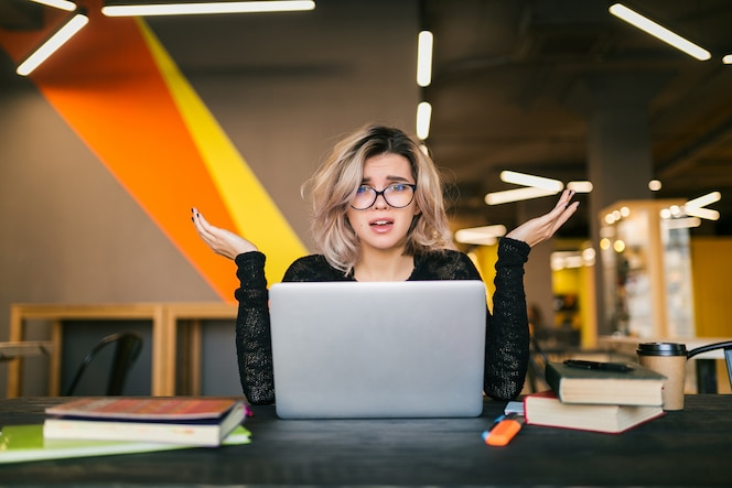 Portret van jonge mooie vrouw met socked gezichtsuitdrukking, zittend aan tafel bezig met laptop in co-working office, bril, stress op het werk, grappige emotie, student in de klas, frustratie