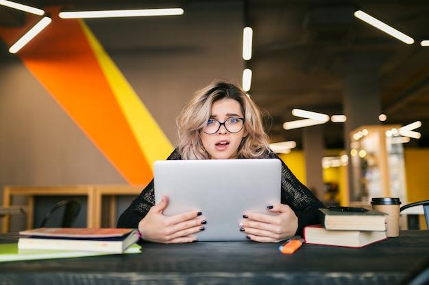 Portret van jonge mooie vrouw met socked gezichtsuitdrukking, zittend aan tafel die op laptop werkt