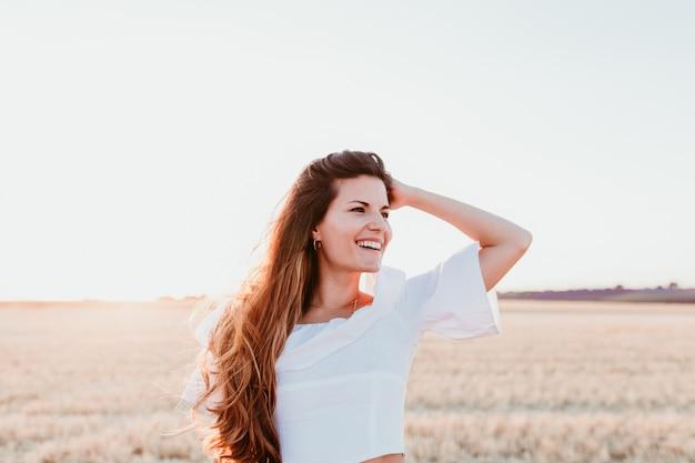 Portret van jonge mooie vrouw op platteland bij zonsondergang
