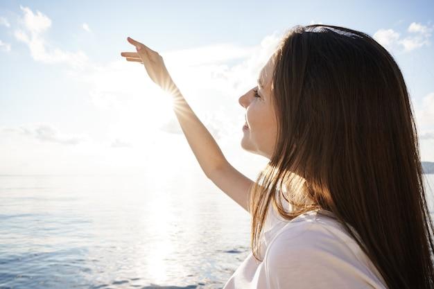 Portret van jonge mooie vrouw staande op de boot tegen zee backgorund