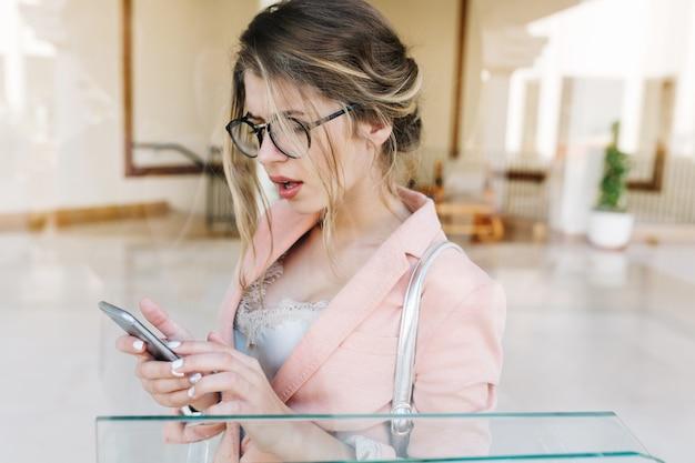Portret van jonge mooie vrouw, stijlvolle zakelijke dame verrast kijken naar smartphone, zilveren telefoon in handen houden, permanent in hal. ze heeft een witte korte manicure en draagt een stijlvol roze jasje.