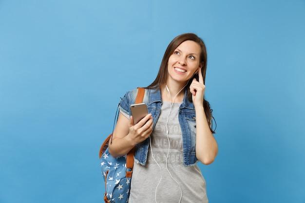 Portret van jonge mooie vrouw student met rugzak en koptelefoon luisteren muziek met mobiele telefoon opzoeken geïsoleerd op blauwe achtergrond. onderwijs aan de universiteit. kopieer ruimte voor advertentie.