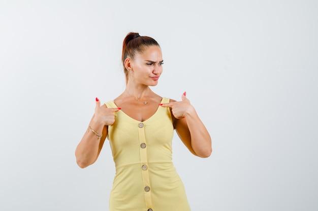 Portret van jonge mooie vrouw wijzend op zichzelf terwijl ze opzij in jurk kijkt en verward vooraanzicht kijkt