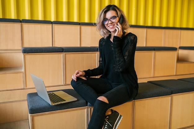 Portret van jonge mooie vrouw zitten in de collegezaal, die op laptop werkt, een bril draagt, een modern auditorium, online studentenstudie, freelancer, glimlachen, praten over de telefoon