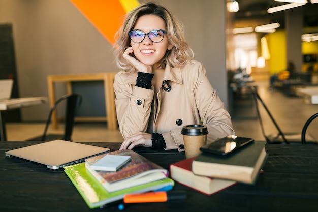 Portret van jonge mooie vrouw zittend aan tafel in trenchcoat bezig met laptop in co-working office