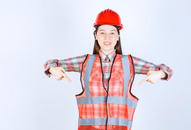 Portret van jonge mooie vrouwelijke ingenieur in helm die ergens naar wijst.