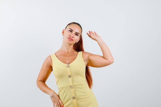 Portret van jonge mooie vrouwelijke zwaaiende hand voor groet terwijl hand op heup in jurk en op zoek naar zelfverzekerd vooraanzicht