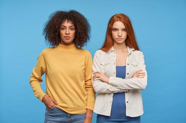 Portret van jonge mooie vrouwen die hun lippen gevouwen houden terwijl ze met kalme gezichten kijken, gekleed in vrijetijdskleding terwijl ze poseren over de blauwe muur