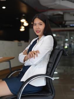 Portret van jonge mooie zakenvrouw glimlachen naar de camera zittend in kantoorruimte