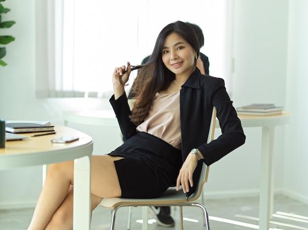 Portret van jonge mooie zakenvrouw glimlachend zittend op de werkplek