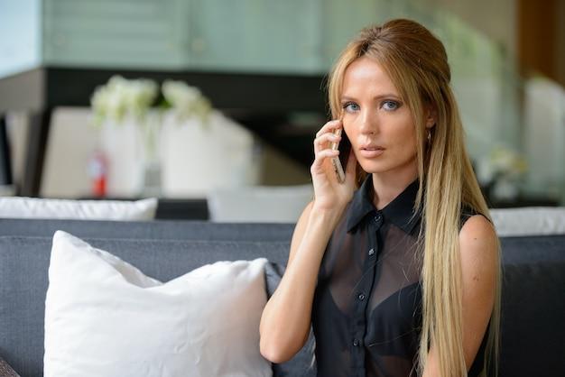 Portret van jonge mooie zakenvrouw met blond haar binnenshuis