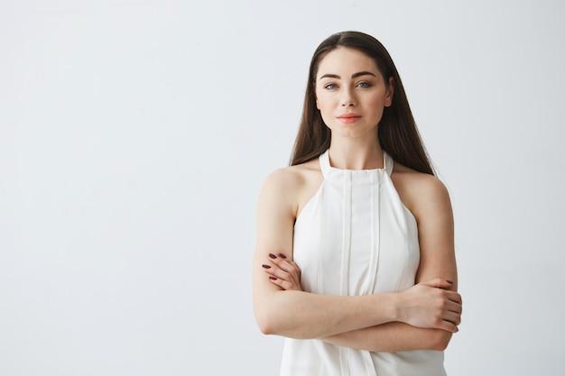Portret van jonge mooie zakenvrouw met gekruiste armen.