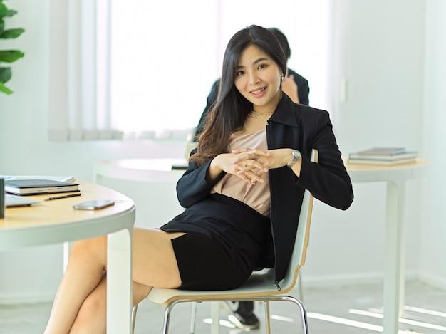 Portret van jonge mooie zakenvrouw zittend op de werkruimte en glimlachen