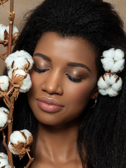 Portret van jonge mooie zwarte met katoenen bloemen. reiniging van huid-, huidverzorging- en cosmetologieconcept