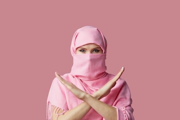 Portret van jonge moslim arabische vrouw draagt kleurrijke hijab tegen roze muur