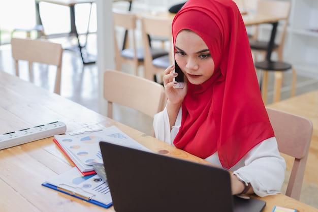 Portret van jonge moslim bedrijfsmensen die rode hijab dragen, die in koffie werken.