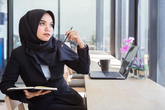 Portret van jonge moslim bedrijfsmensen die zwarte hijab dragen, die in koffie werken.