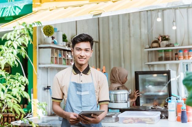 Portret van jonge moslimmannen die eten en drinken verkopen in zijn kleine winkel gemaakt van vrachtwagencontainerdoos