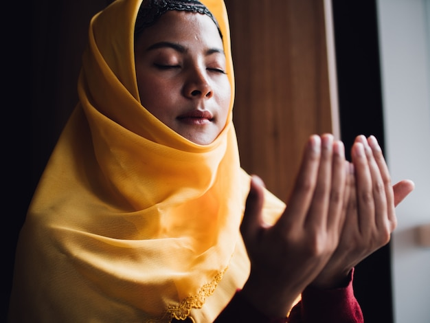 Portret van jonge moslimvrouw bidden in vintage kleurtoon