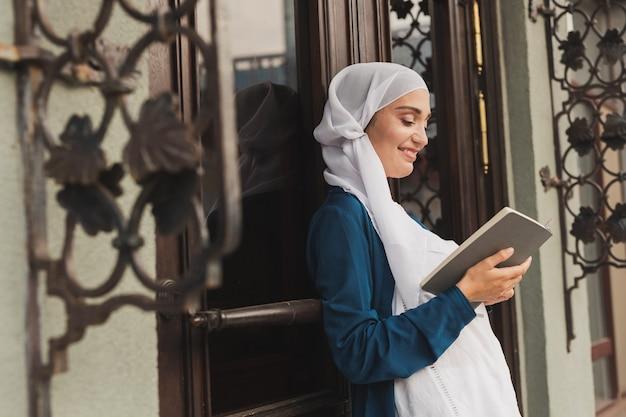 Portret van jonge moslimvrouw die hijab-leesboek buitenshuis draagt wearing