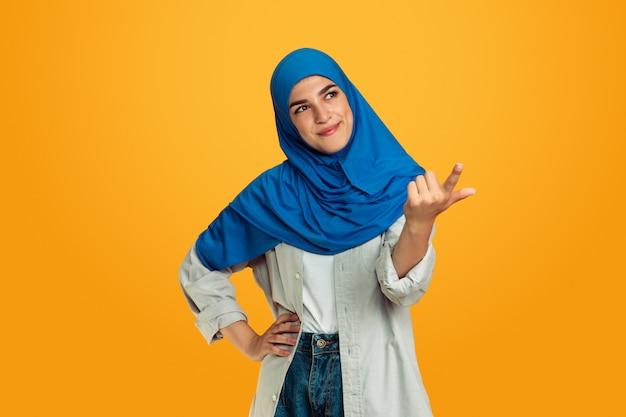 Portret van jonge moslimvrouw die op gele studioachtergrond wordt geïsoleerd