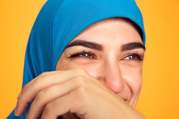 Portret van jonge moslimvrouw geïsoleerd op geel