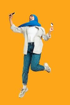 Portret van jonge moslimvrouw geïsoleerd op gele studio background