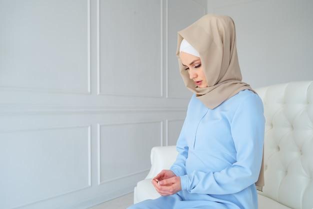 Portret van jonge moslimvrouw in beige hijab en traditionele kleding bidden