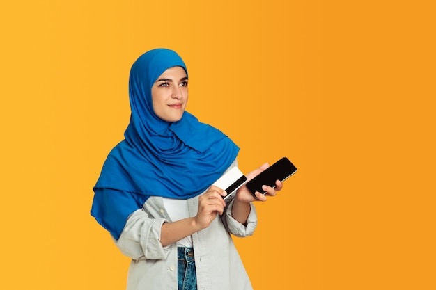 Portret van jonge moslimvrouw op gele muur Gratis Foto
