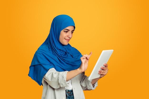 Portret van jonge moslimvrouw op gele muur