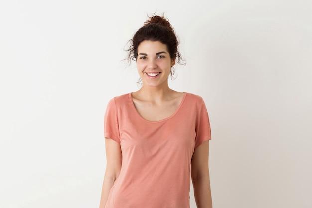 Portret van jonge natuurlijk ogende glimlachende gelukkige hipster mooie vrouw in het roze overhemd stellen geïsoleerd op witte studioachtergrond