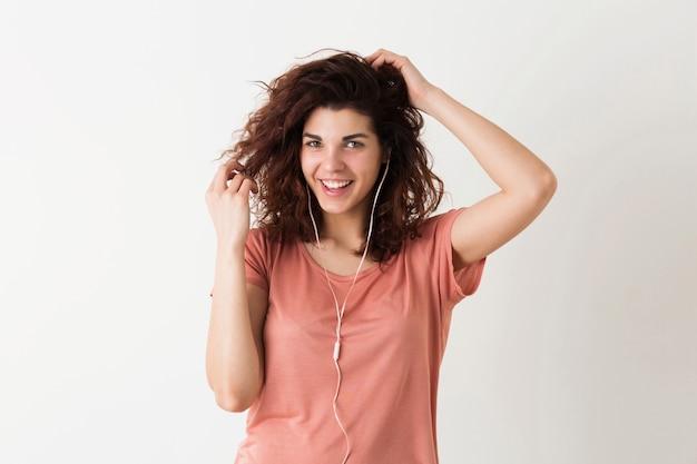 Portret van jonge natuurlijk ogende lachende gelukkig hipster mooie vrouw met krullend kapsel in roze shirt poseren geïsoleerd op witte studio achtergrond, luisteren naar muziek in oortelefoons