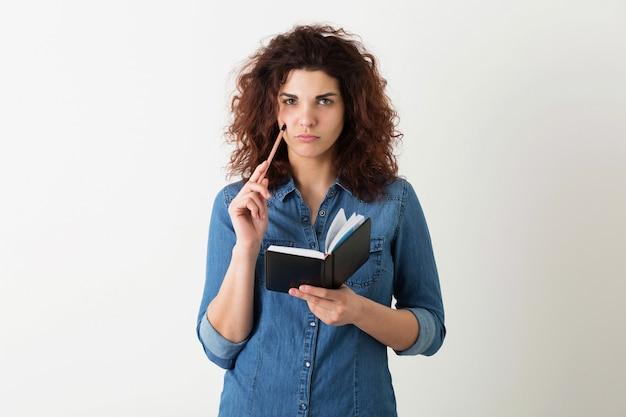 Portret van jonge natuurlijke glimlachende mooie vrouw met krullend kapsel in denimoverhemd het stellen met notitieboekje en geïsoleerde pen, student leren, die op probleem denken