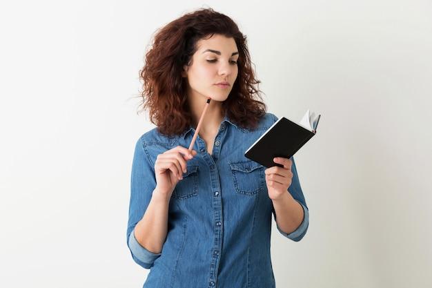Portret van jonge natuurlijke hipster lachende mooie vrouw met krullend kapsel in denim overhemd poseren met notitieboekje en pen geïsoleerd op witte studio achtergrond, student leren, denken over probleem