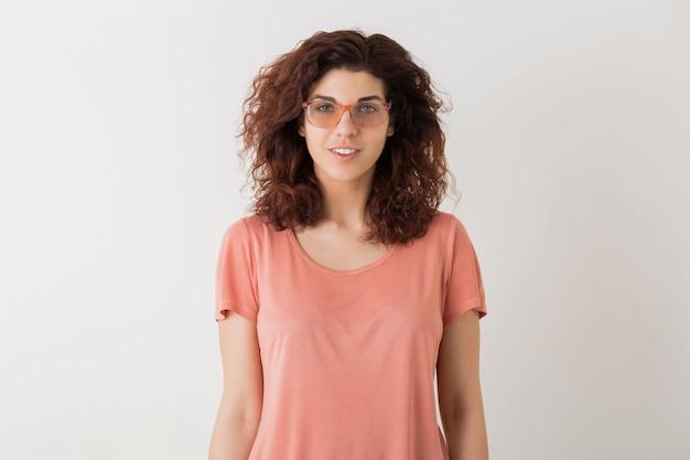 Portret van jonge natuurlijke lachende hipster mooie vrouw met krullend kapsel in roze shirt poseren dragen van een bril geïsoleerd op witte studio achtergrond