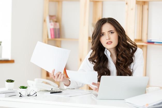 Portret van jonge onderneemster die in haar bureau met ernstige gezichtsuitdrukking met documentverslag werkt