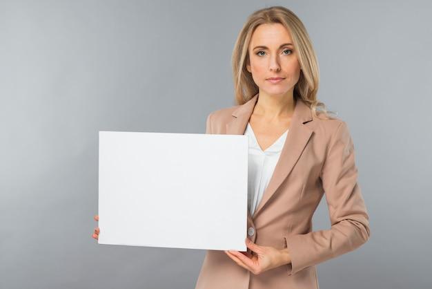 Portret van jonge onderneemster die leeg wit aanplakbiljet toont tegen grijze achtergrond