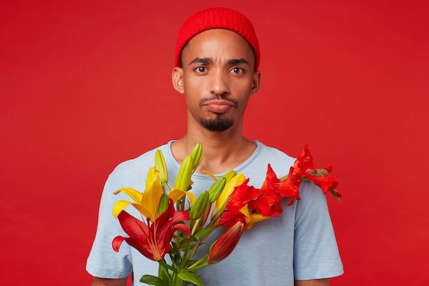 Portret van jonge ongelukkig aantrekkelijke kerel in rode hoed en blauw t-shirt, houdt een boeket in zijn handen, kijkt naar de camera met droevige uitdrukking, staat over rode achtergrondgeluid.