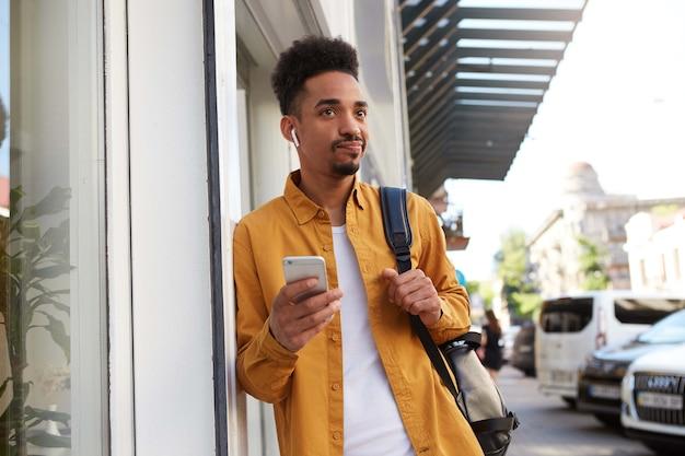 Portret van jonge ontevreden afro-amerikaanse student in geel overhemd lopend onderaan de straat, houdt telefoon, wachtende vrienden, kijkt woedend.