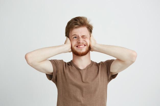 Portret van jonge ontevreden boze man met baard sluitende oren.