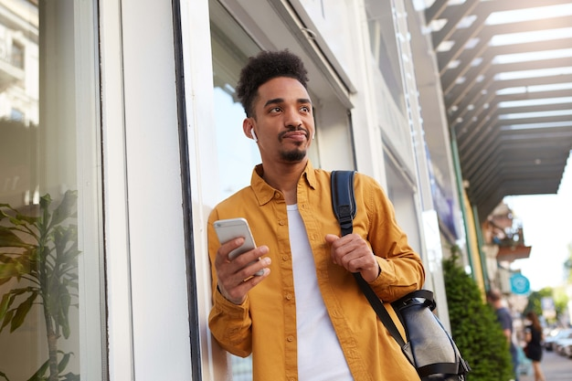 Portret van jonge ontevreden donkere man, chatten aan de telefoon met zijn vrienden, op zoek met een verontwaardigde uitdrukking, zijn vriendin is weer te laat.