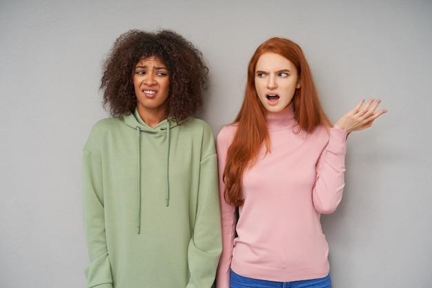 Portret van jonge ontevreden krullende donkerhuidige brunette vrouw in groene hoodie fronst haar gezicht terwijl poseren over grijze muur met verbaasde roodharige mooie vrouw