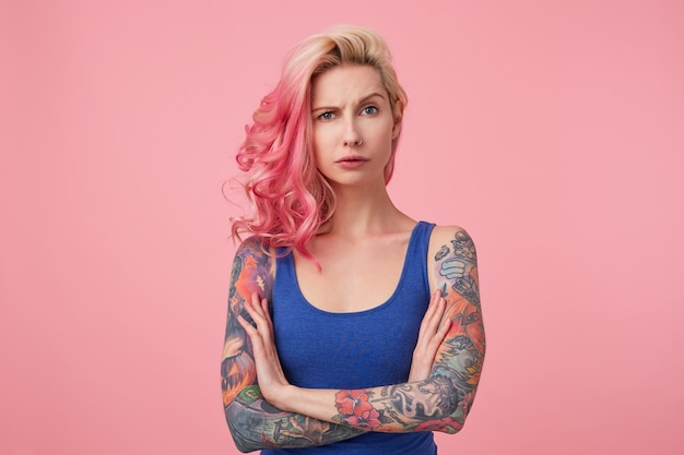 Portret van jonge ontevreden schoonheidsvrouw met roze haar, fronst en staat met gekruiste armen, ziet er verdrietig uit, draagt een blauw shirt. mensen en emotie concept.