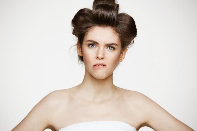 Portret van jonge ontevreden vrouw in haarkrulspelden. schoonheid cosmetologie en spa.