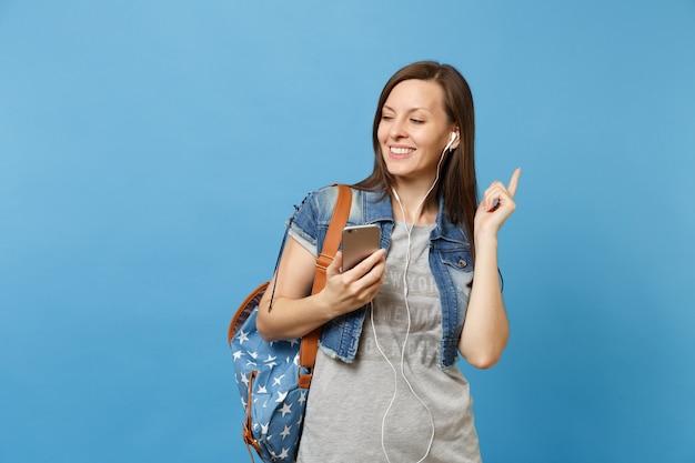 Portret van jonge ontspannen lachende vrouw student met rugzak en koptelefoon luisteren muziek met mobiele telefoon geïsoleerd op blauwe achtergrond. onderwijs op de middelbare school. kopieer ruimte voor advertentie.
