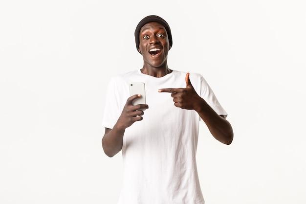 Portret van jonge opgewonden afro-amerikaanse kerel die smartphone-app aanbeveelt, wijzende vinger op mobiele telefoon met verbaasd en blij gezicht.